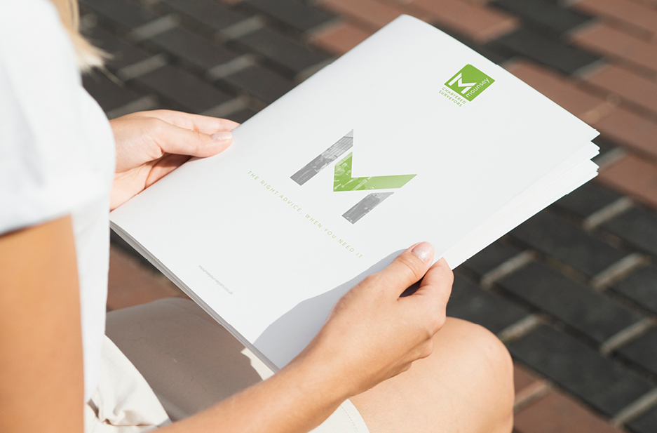 Person holding Mounsey corporate brochure
